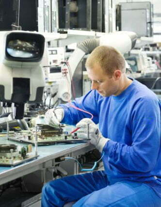 Operaio a lavoro su componenti elettronici, vestito di felpa e pantaloni antinfortunistici certificati ESD